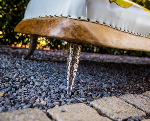 Close up zilveren poot/voet design sofa met teak hout en lederen zitting